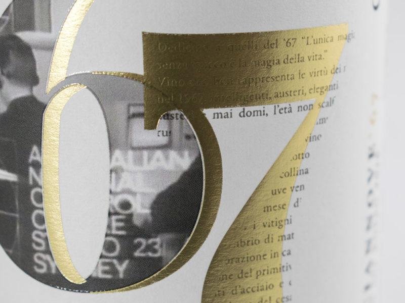 Closeup di una etichetta di vino rosso con lamina oro, rilievo serigrafico e carta bianca su sfondo bianco