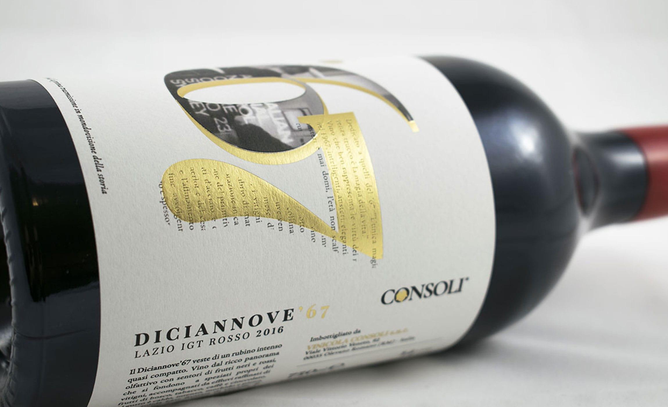 Bottiglia di vino rosso adagiata su un telo bianco su sfondo bianco. Etichetta di carta bianca con lamina oro e rilievo serigrafico.