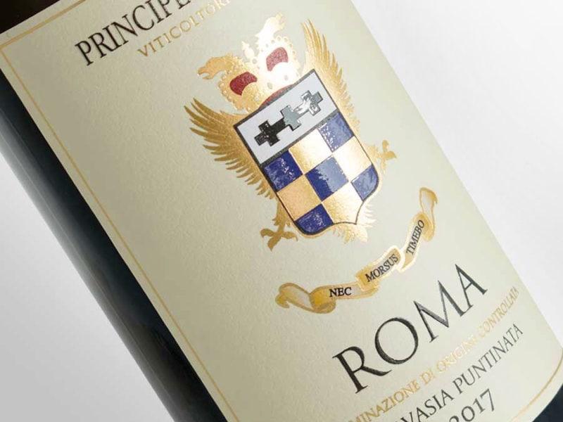 Closeup di una etichetta di vino colorata con stemma nobiliare in lamina oro su carta gialla. Bottiglia su sfondo bianco.