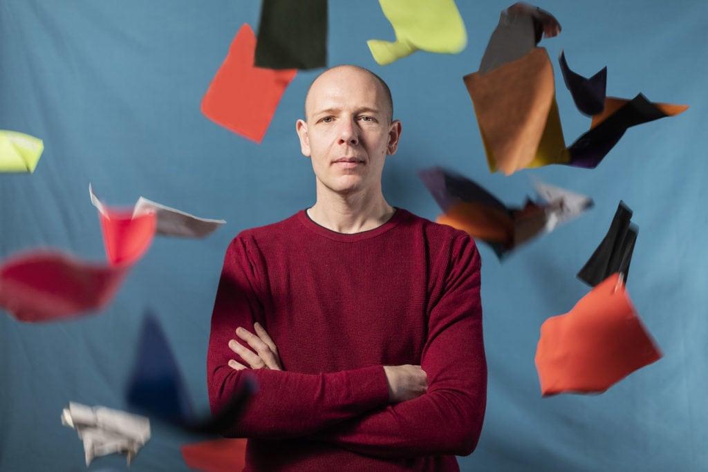Ritratto fotografico di uomo su sfondo celeste con fazzoletti che volano
