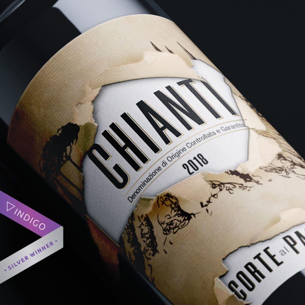 Close up di bottiglia di vino rosso Chianti con etichetta in lamina oro ed effetto strappo.