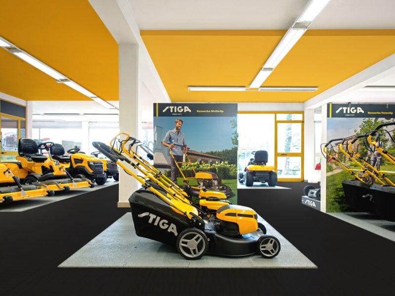 Interno negozio di motoseghe e tosaerba per giardino con soffitto giallo.